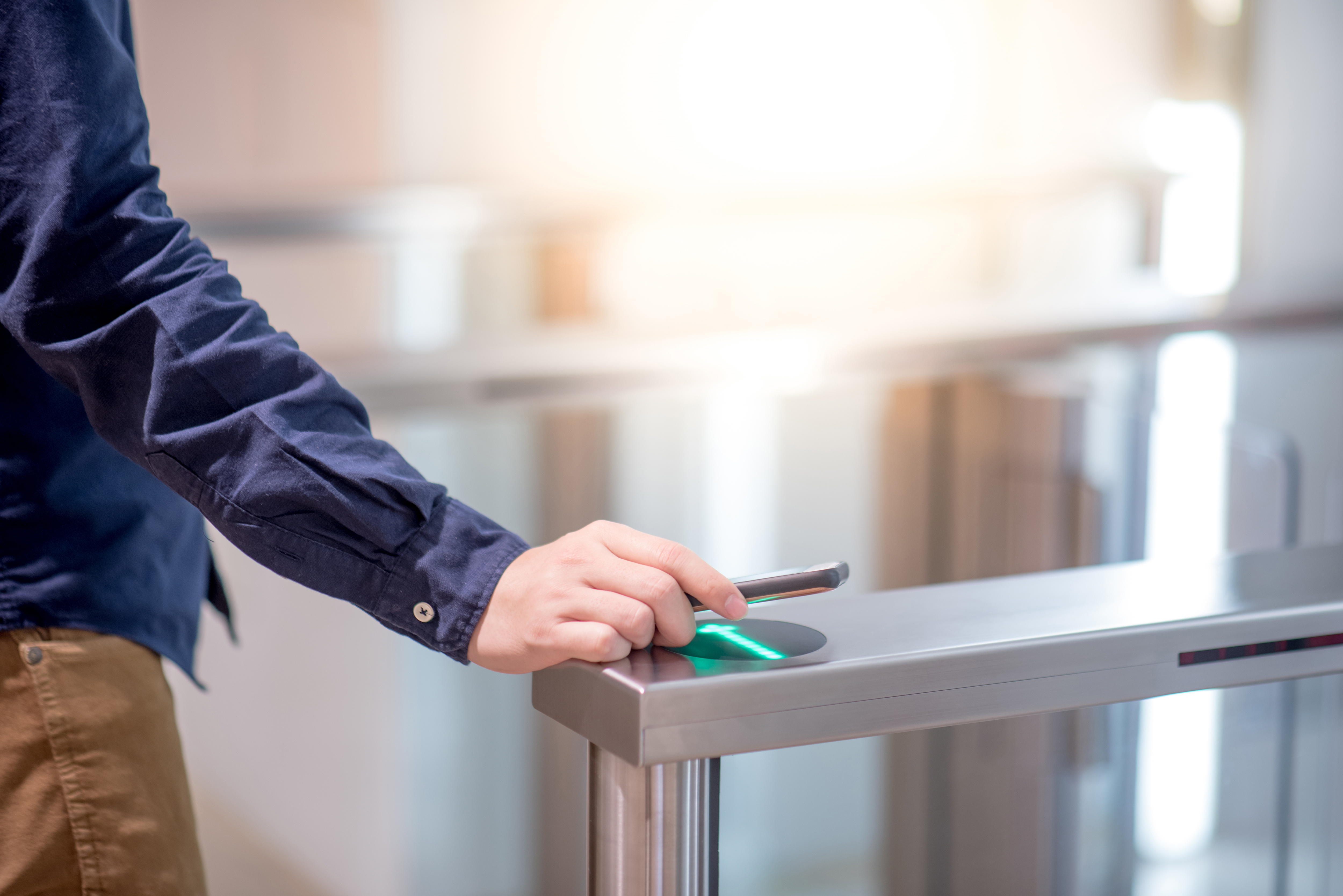 Man touching reader with phone to access an entry point