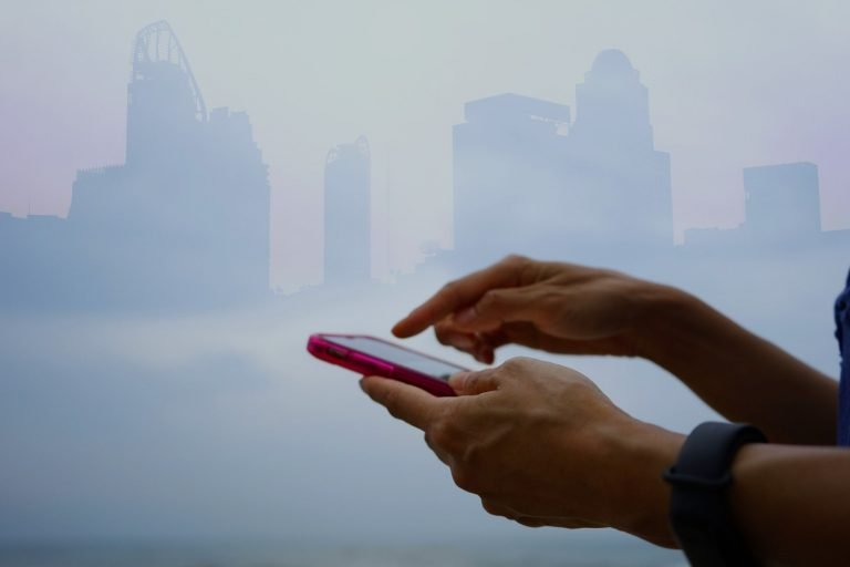 woman holding smartphone with buildings in background